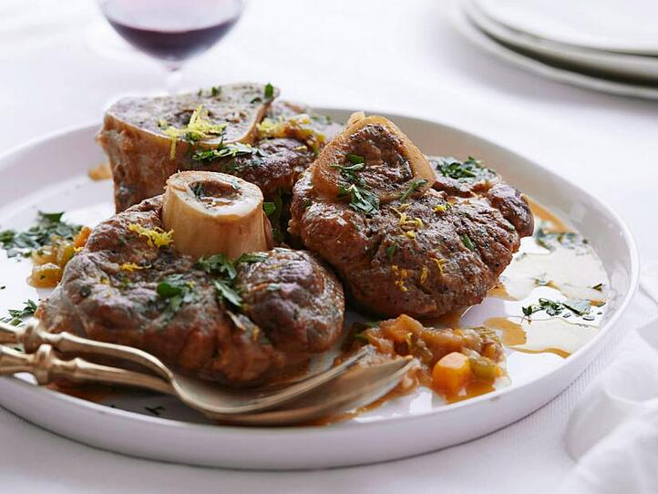 Osso Buco on a white plate in a bright lit room