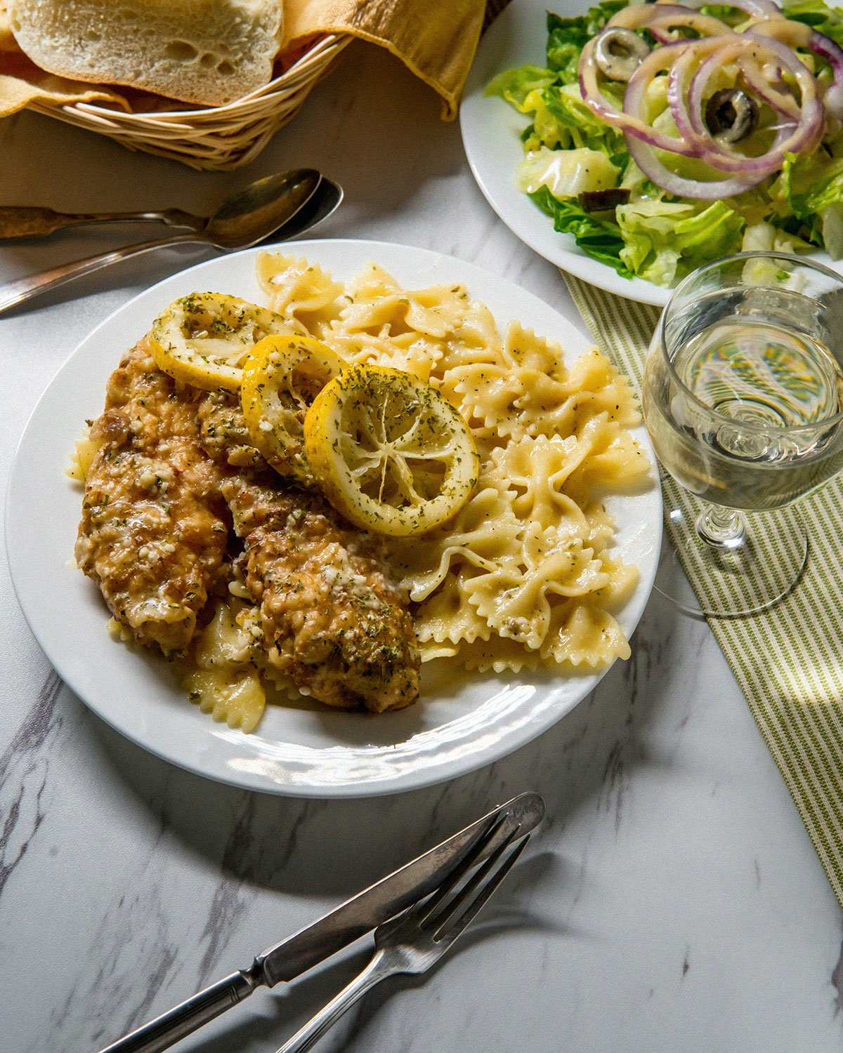 chicken francese with salad on dinner table