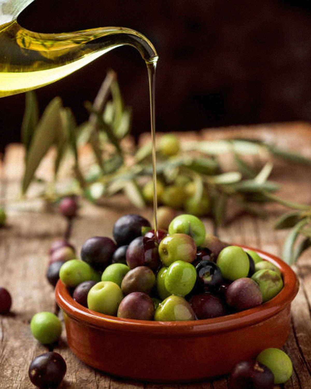 pouring olive oil on top of olives in a small bowl