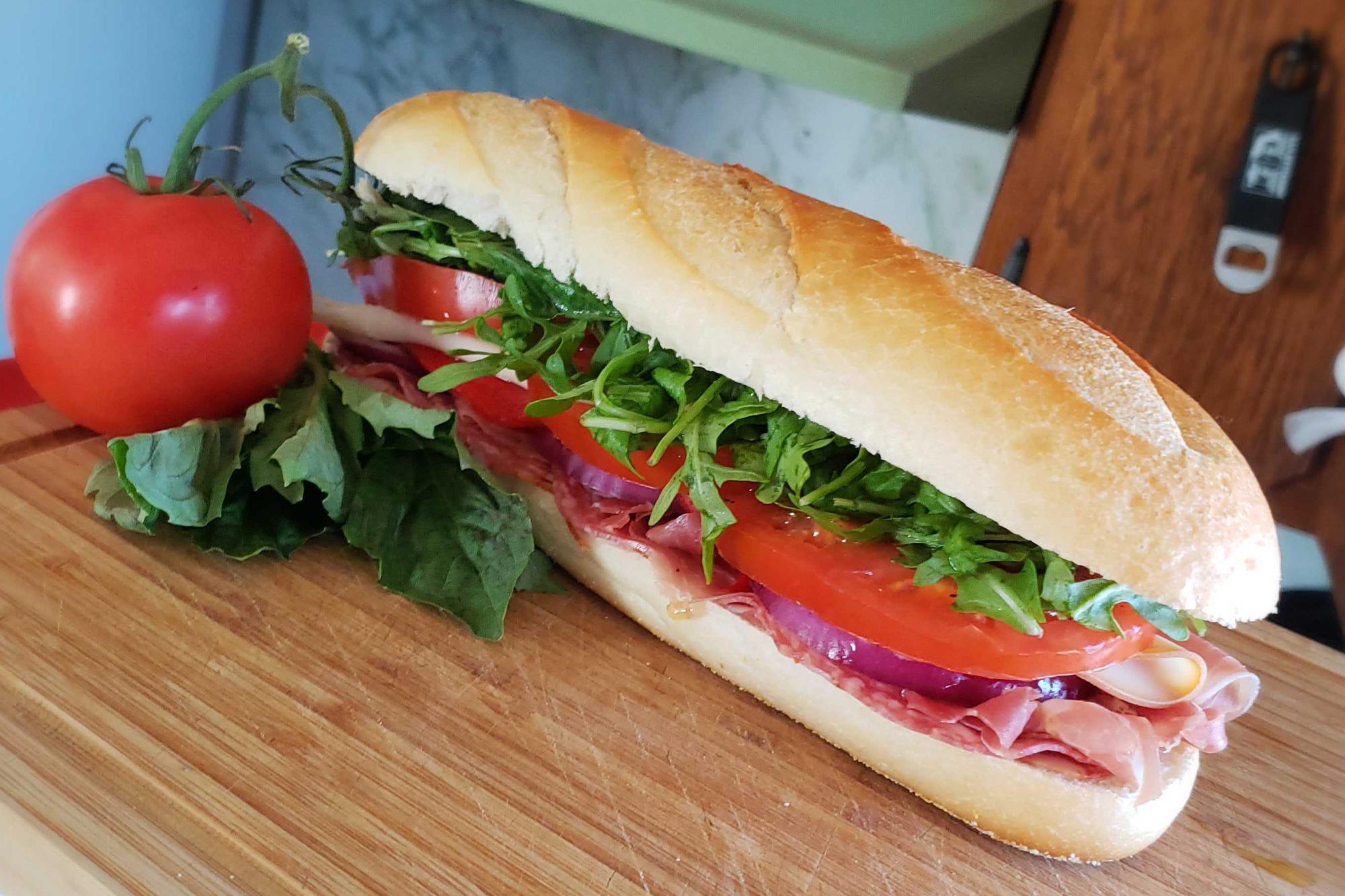 Close up of Super Italian Sub on cutting board with full tomato