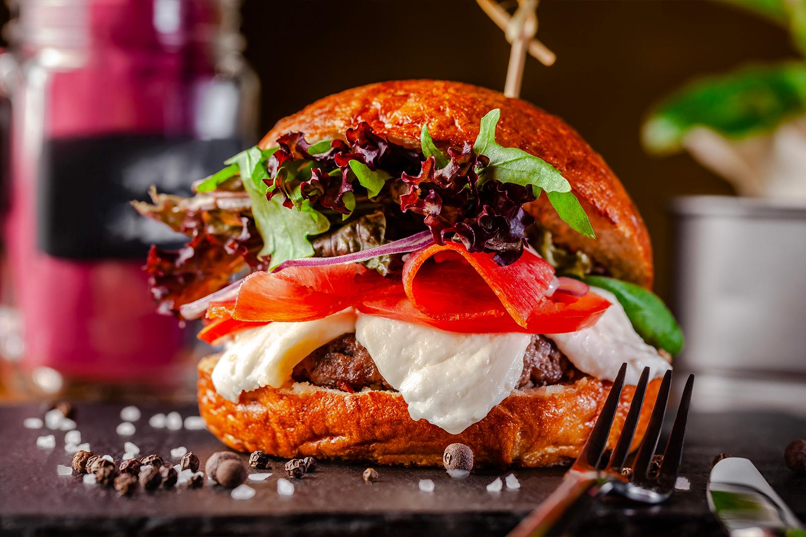 Hamburger with mozzarella and tomatoes on brioche bun