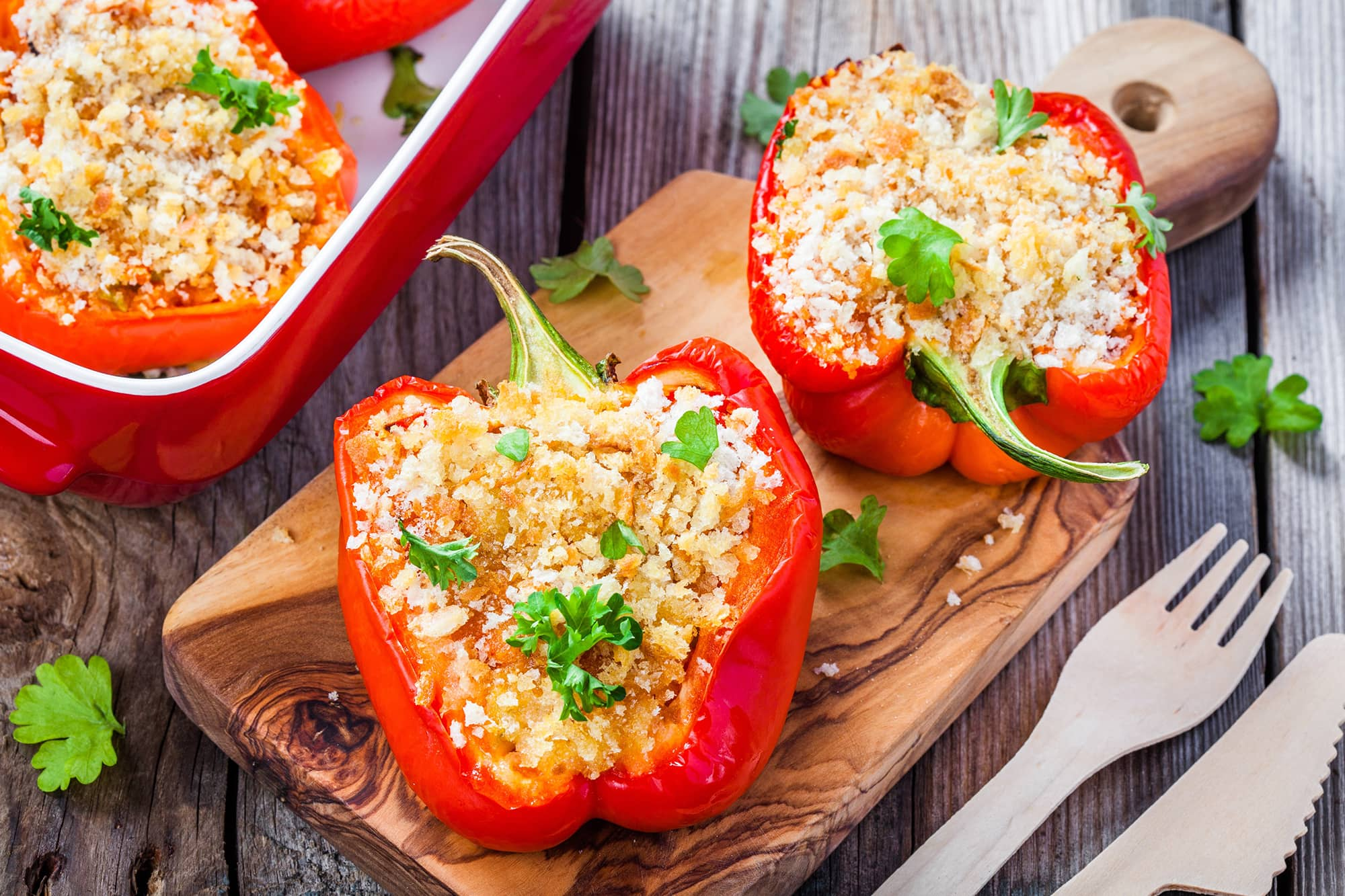 Vegetarian Stuffed Peppers on cutting board with cutlery on the side
