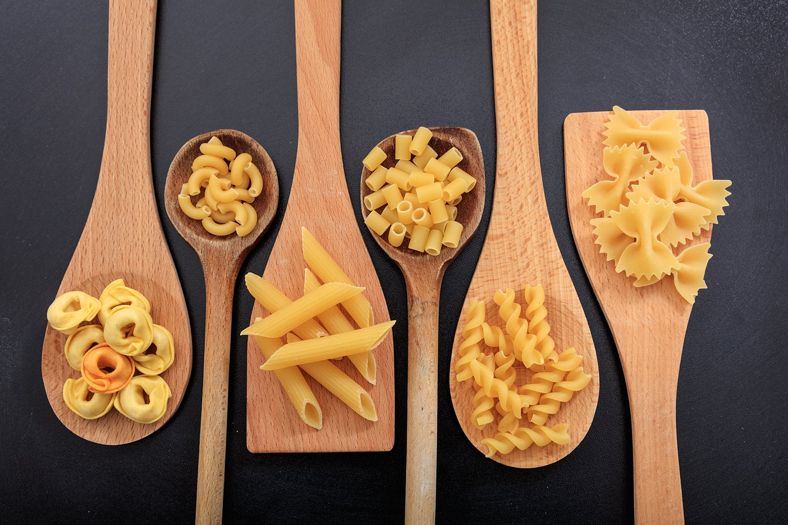 Different types of pasta shapes sitting on wooden spatulas