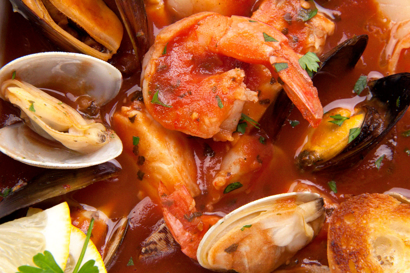upclose photo of shrimp and clams in pasta sauce