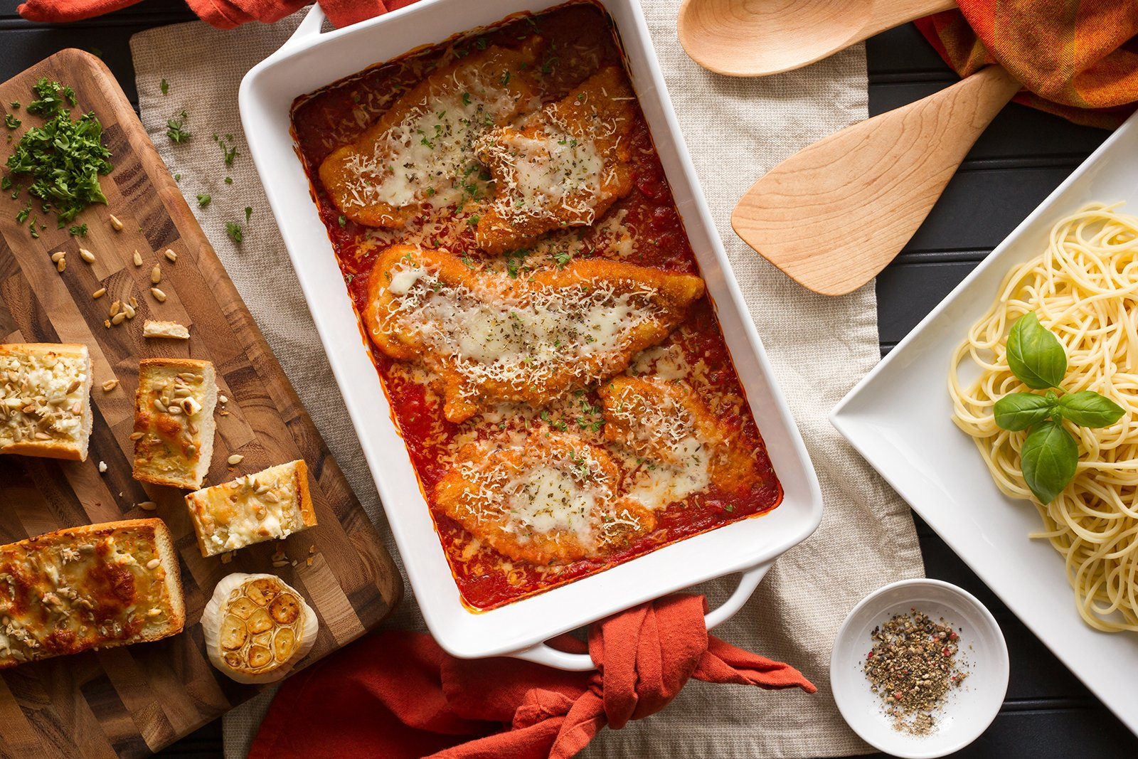 Dish with Chicken Parmigiana and Garlic Bread to the left