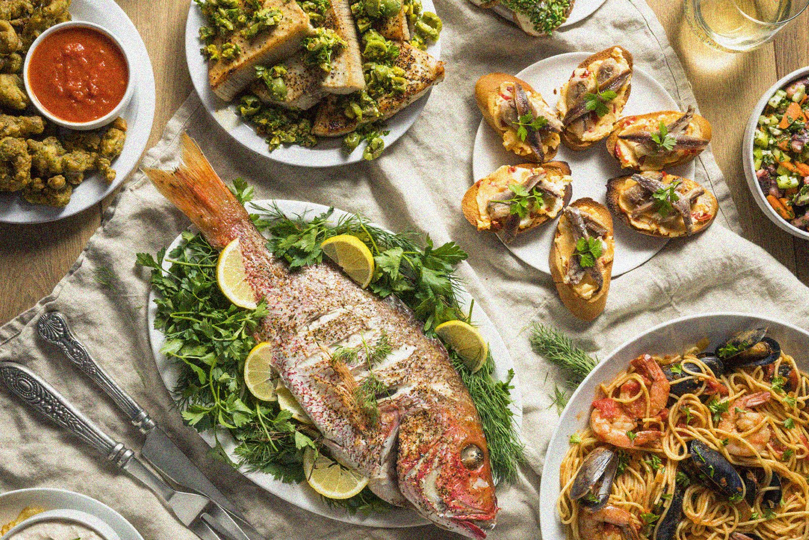 assortment of dishes on a table including fish, spaghetti with seafood, bread