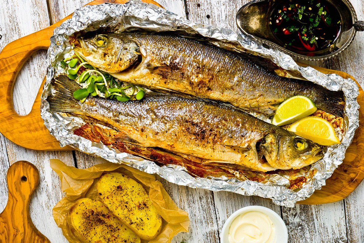 roasted branzino on a wood cutting board with lemons on the side