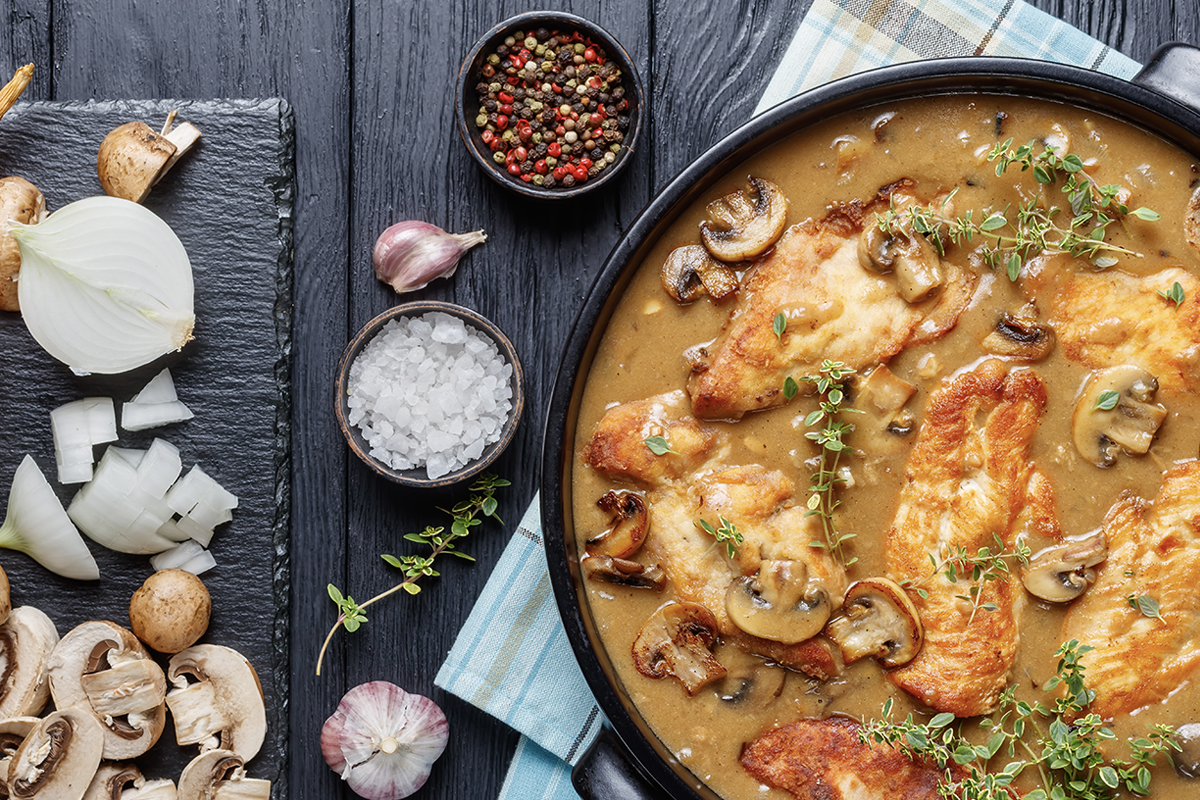 Chicken marsala in a pot with ingredients laying to the right