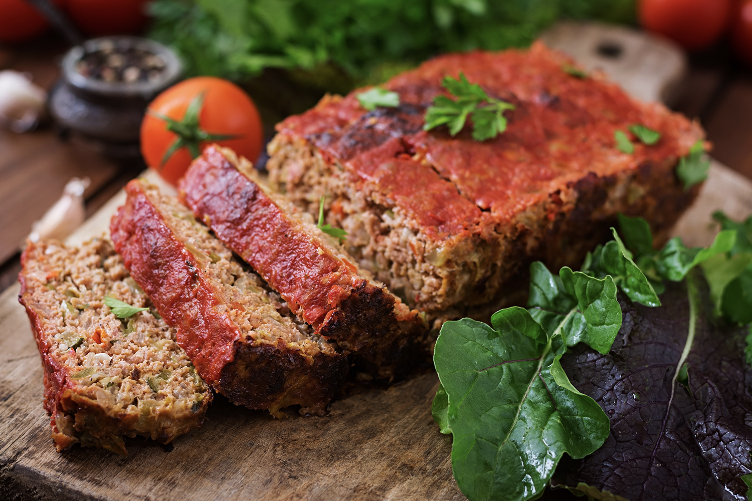 Italian Meatloaf with pasta sauce on top and italian condiments surrounding dish