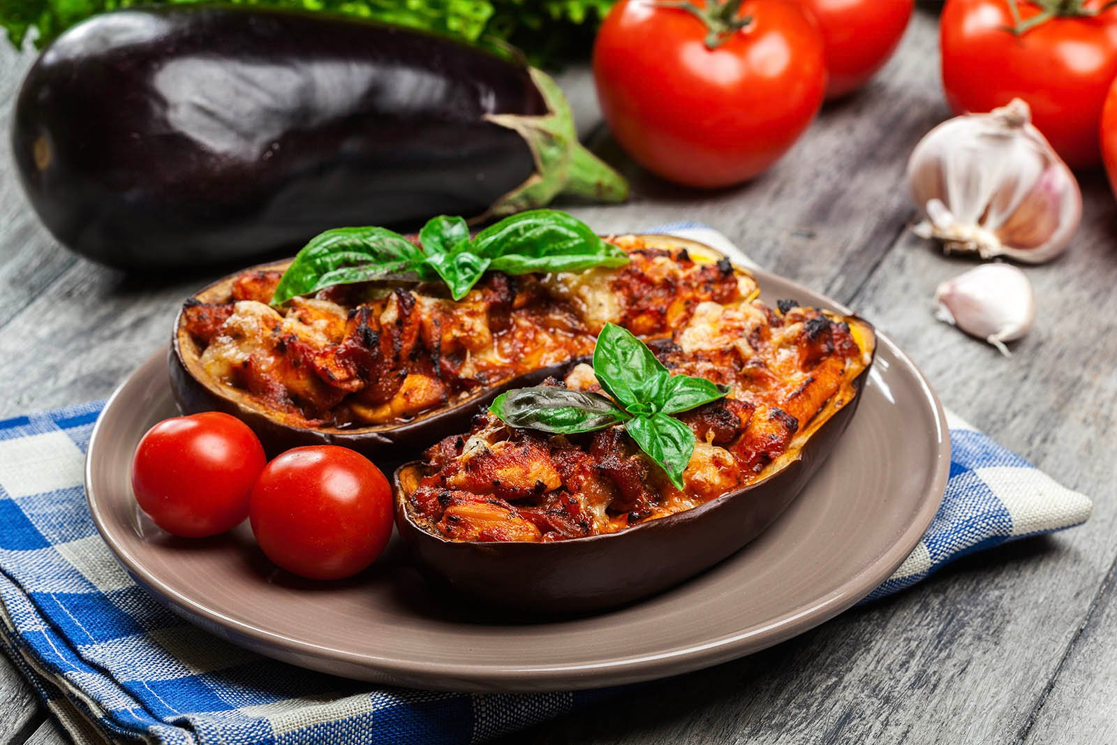 stuffed eggplant on a brown plate with cherry tomatoes and basil leaves on a table with eggplant, tomatoes, and garlic in the background